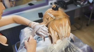 El estudio de belleza estilista hace que la pintura del cabello se convierta en mechones rubios. video