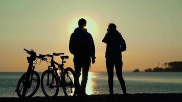 The silhouettes of two people with bicycles on the beach