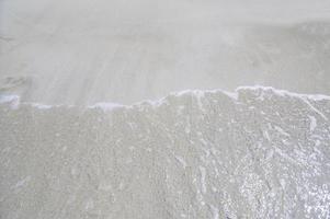 agua de mar en la playa de arena foto