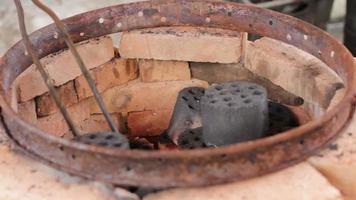 Kohle im Ziegelkocher wechseln