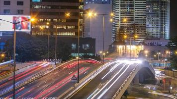 timelapse do distrito financeiro de hong kong à noite. edifício corporativo na parte de trás e tráfego intenso na estrada principal na hora do rush