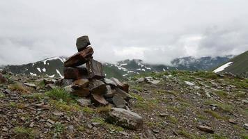 pilhas de pedras marcam o caminho certo em altas montanhas nevadas