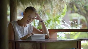 Woman using tablet PC sitting outdoor in tropics video