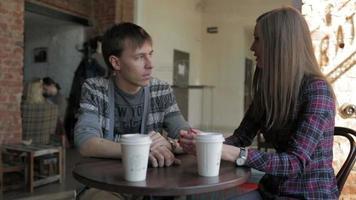 jovem casal em uma cafeteria conversando