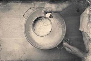 tamizar la harina para amasar. en blanco y negro