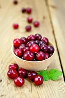 Cranberries in a wooden bowl on the board