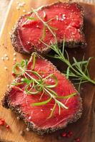 raw beef steak with spices and rosemary on wooden background photo