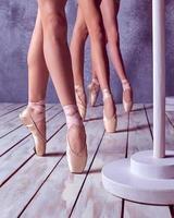 los pies de una joven bailarina con zapatillas de punta foto