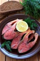 Pink salmon slices on the brown ceramic plate photo