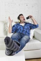 hombre escuchando música sosteniendo un teléfono móvil como micrófono foto