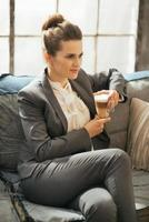 Business woman with coffee latte sitting on divan in apartment photo