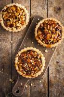 Three tart pies on a wooden paddle and wooden surface photo