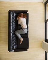 Aerial view of young female sleeping on couch photo