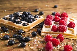 Waffles with whipped cream and raspberries and cranberries photo