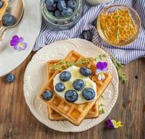 Homemade fresh crispy waffles for breakfast with blueberries and honey