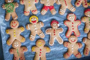 Raw gingerbread men with glaze on a baking sheet