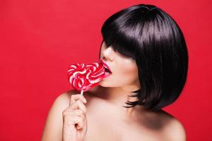 Young woman with heart shaped pink lollipop. on red background