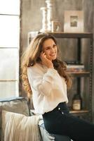 happy young woman talking cell phone in loft apartment photo