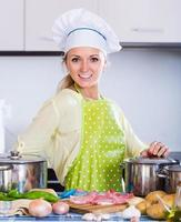 Portrait of  blonde girl preparing meat indoors photo