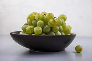 uvas en un plato sobre fondo neutro