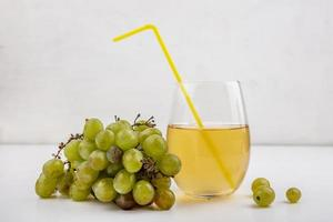 Grape juice and fruit on neutral background