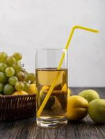 Grape juice and fruit on wooden surface and neutral background