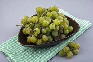 Grapes in bowl on plaid cloth on gray background