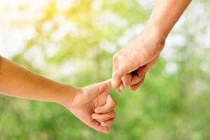 Adult holding child's hand isolated on background