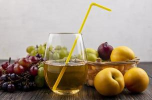 Side view of juice and fruits on wooden surface and neutral background