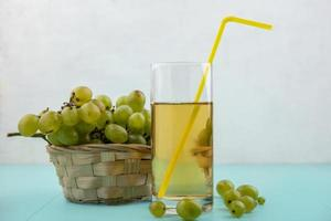 Side view of white grapes and juice on blue surface