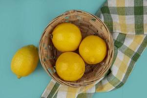 Top view of basket of lemons on plaid cloth and blue background