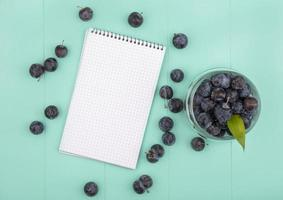 Top view of berries and a notepad on teal background with copy space