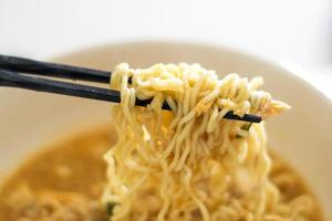Black wooden chopsticks holding noodles photo