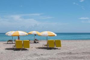 Miami, Florida, 2020 - Beachgoers with yellow umbrella and chairs on beach