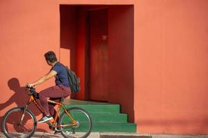 Miami, Florida, 2020 - Man riding bicycle in front of colorful building photo