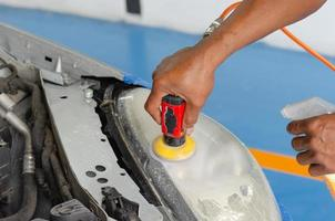 Close-up of person cleaning headlight