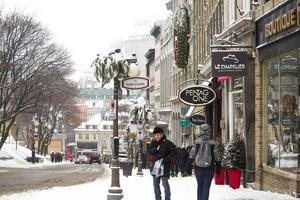 Quebec, Canada, 2020 - People walking in snow near shops