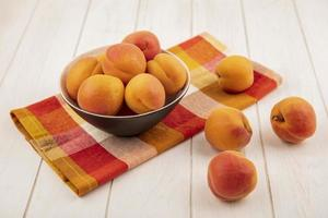 Peaches in a bowl on plaid cloth on wooden background