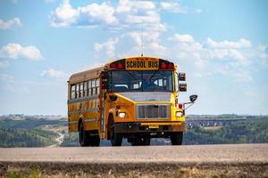 Alberta, Canada, 2020 - Yellow school bus on road photo