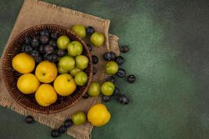 Food photography flat lay of fresh fruit on green background with copy space