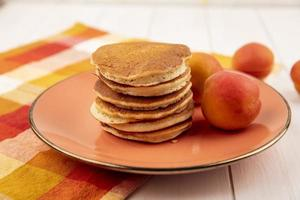 Fresh pancakes with fruit on wooden background