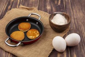 Fresh pancakes with eggs on wooden background photo