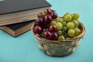 Uvas en canasta con libros sobre fondo azul. foto