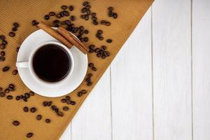 Food photography of a cup of coffee with cinnamon and roasted beans on wooden background