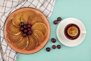 Tortitas con cerezas y té sobre fondo azul.