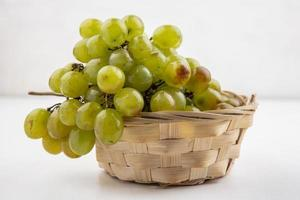White grapes in a basket on white background