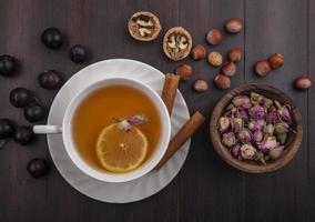 Fotografía de alimentos laicos plana de una taza de té y nueces y bayas sobre fondo de madera