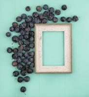 Top view of a wooden picture frame and berries on teal background with copy space