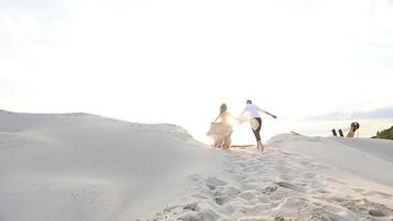 Beautiful young high-fashion dressed couple running through the sandy beach on sunset and having fun together