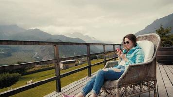 Mujer turista vestida con ropa elegante graba videos del hermoso paisaje de montaña en el teléfono celular, chica hipster tomando fotos con la cámara del teléfono móvil mientras está sentada cerca de las montañas en un día fresco de primavera